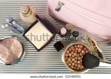 Cosmetics on the table. Basic colors pink and gold. Powder, skin cream, lipstick, handbag, vanity case, brush, eyeliner