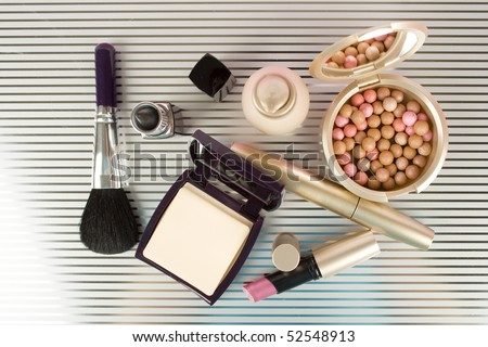 Cosmetics on the table. Basic colors pink and gold. Powder, skin cream, lipstick, handbag, vanity case, brush, eyeliner