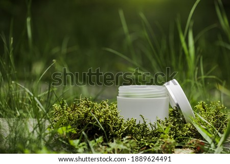 Cosmetics, skin care, beauty, body treatment concept. open White cosmetic jar, tube, bottle on green moss background. Top view. Mock-up. Vegan eco friendly. Biophilic design.