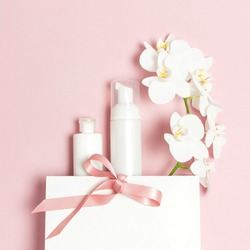 Cosmetics SPA branding mock-up. Flat lay top view White cosmetic bottle containers gift bag White Phalaenopsis orchid flowers on pink background. Natural organic beauty product concept