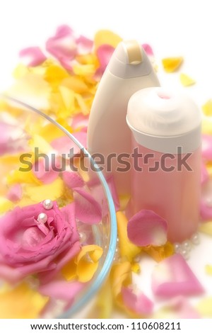 Cosmetics with pink and yellow roses and petals