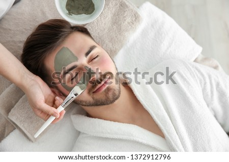 Cosmetologist applying mask on client's face in spa salon, above view