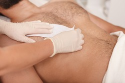 Cosmetologist doing waxing on torso of unrecognizable male client