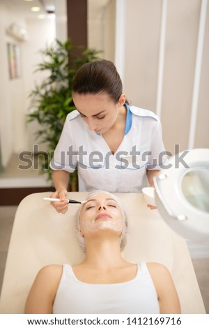 Cosmetologist feeling involved. Cosmetologist feeling involved in putting cleansing mask on face of client #1412169716
