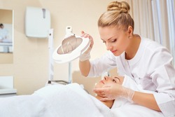 Cosmetologist is a professional with a patient in the office of