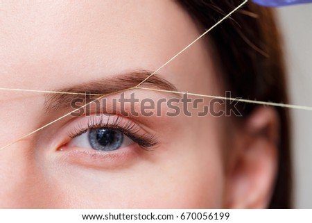 Shutterstock Cosmetologist plucks client eyebrows by thread