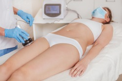 Cosmetologist using rf-lifting device on the hips of female client at beauty salon