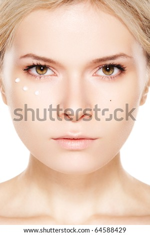 Cosmetology & cosmetic. Close-up portrait of beautiful woman which applying cream near eyes