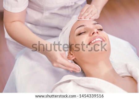 Cosmetology. Cosmetologist hands cleanse the skin. Facial skin care. Smiling girl procedure. Visiting cosmetology clinic
