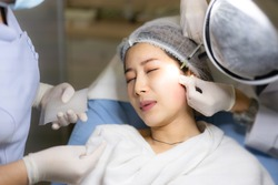 Cosmetology doctor makes beauty injections of botulinum toxin on face to a woman,Young asian woman in a beauty salon.Cosmetology skin care.