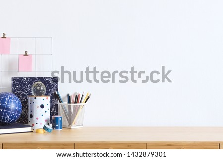 Cosmic and stylish home office interior with wooden desk, cool office accessories, tapes, supplies, notebooks, memo sticks, pencils. Modern home decor. Minimalistic concept. Template. Copy spce.