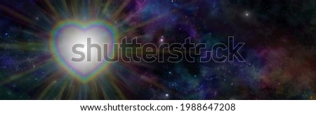 Cosmic Rainbow Heart Light background - dark starry night deep space background and rainbow coloured heart with  rainbow coloured light radiating outwards and copy space on right