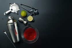 Cosmopolitan cocktail and bar equipments, stainless steel cocktail shaker and jigger, bar spoon with strainer, the lemons and ice tongs with ice cubes on the table