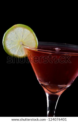 cosmopolitan cocktail served in a chilled martini glass garnished with a lime wheel, served on a dark bar