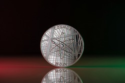Cosmos ATOM Cryptocurrency physical coin placed on reflective surface and lit with the green and red lights.