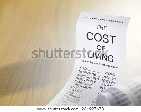Cost of living shopping list showing the expense of home finance with copy space on wooden background
