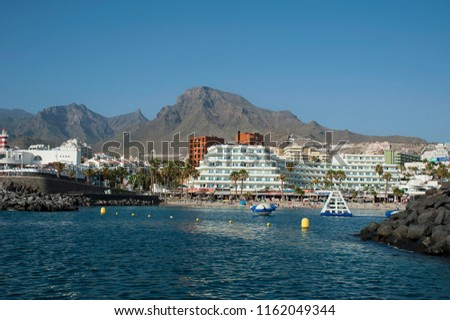 Costa Adeje, Tenerife, Canary Islands, Spain - July 6, 2018: view from the ocean of the popular resort of Las Americas for its port restaurants, pubs and bars, entertainment and night life venues. #1162049344