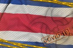 Costa Rica flag and Covid-19 biohazard symbol with quarantine orange tape and stamp. Coronavirus or 2019-nCov virus concept