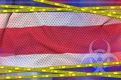 Costa Rica flag and Covid-19 quarantine yellow tape. Coronavirus or 2019-nCov virus concept