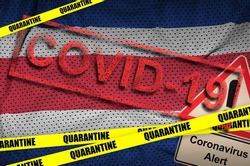 Costa Rica flag and Covid-19 quarantine yellow tape with red stamp. Coronavirus or 2019-nCov virus