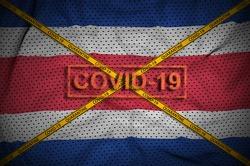 Costa Rica flag and Covid-19 stamp with orange quarantine border tape cross. Coronavirus or 2019-nCov virus concept