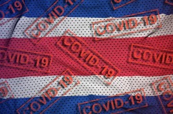 Costa Rica flag and many red Covid-19 stamps. Coronavirus or 2019-nCov virus concept