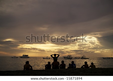 Costa Rica sunset with Boats and silhouettes of people on beach