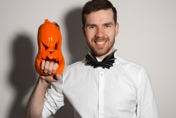 Costume for Halloween masquerade, Young attractive guy in white shirt with black bat tie with pumpkin evil smile in hands on white background