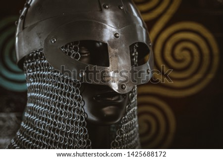 Costume Vikings, viking helmet with chain mail on a red shield with golden shapes of sun, weapons for war #1425688172