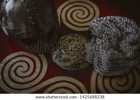 Costume Vikings, viking helmet with chain mail on a red shield with golden shapes of sun, weapons for war #1425688238