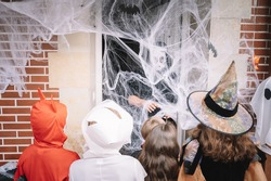 Costumed kids trick-or-treating on halloween behind a web