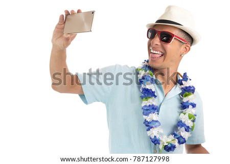 Costumed man grimaces for the photo. Selfie. He wears a hat, sunglasses and a necklace of flowers. Young latin american man wearing blue shirt. Isolated on white background.