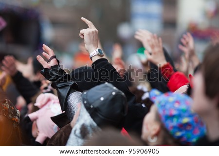 costumed people raise their arms at the street carnival