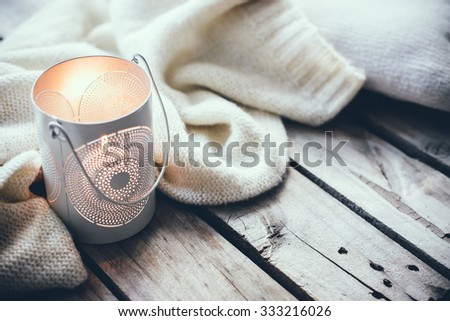 Cosy and soft winter background, knitted sweater and candles on an old vintage wooden board. Christmas holidays at home.