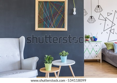 Cosy armchair and minimalistic coffee tables at the black wall background