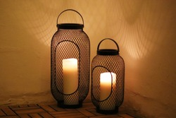 Cosy atmosphere by a candle holder with big White candles in the dawn