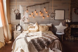 Cosy bedroom with eco decor. Wood and nature concept in interior of room. Scandinavian interior, real photo. Hygge decoration.