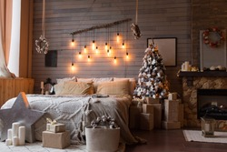 Cosy bedroom with eco decor. Wood and nature concept in interior of room. Scandinavian interior with christmas tree, real photo. Hygge decoration. Christmas concept.