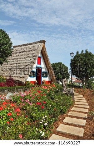 Cosy chalet with a triangular thatched roof. Before the house - garden with beautiful flower beds. Madeira Island, the city Santana