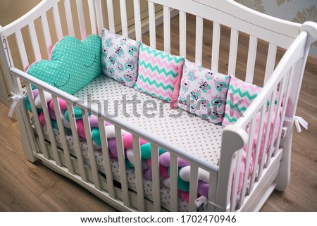 Cosy children 's tree white crib with multicolored soft cushions, white to the point with a simple, pigtail and cans. children's room