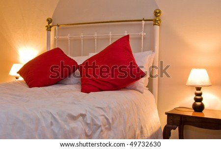 cosy country bedroom with white bedding and red pillows with bedside lamp