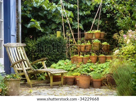 Cosy garden with wooden relax chair - stock photo