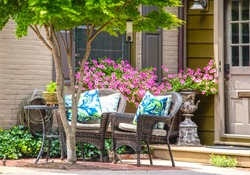 Cosy outside seating area with wicker chairs with bright pillows in front of potted  pink pansies under tree near window and door with cat peeking out and bird feeder overhead