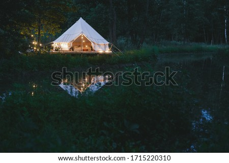cosy trendy design and decorated bell tent in nature Glamping (glamorous camping) near river and forest