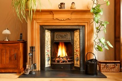Cosy winter living room fireplace, with open fire with real flames burning coal, UK home interior