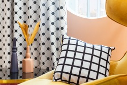Cosy yellow armchair with striped black and white pillow by the oval window with polka dotted curtain and glass table with two vases with dry flowers.