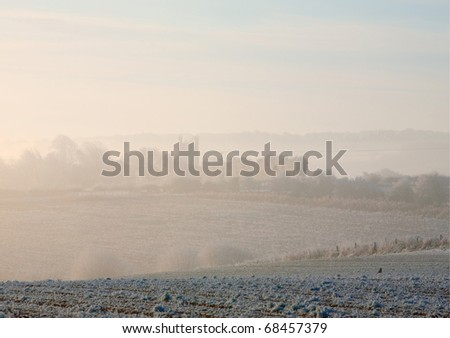 Cotswold winter morning looking towards Chipping Campden through the mist. - stock photo