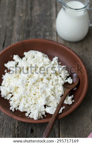 Cottage cheese and a jug of milk on a wooden background