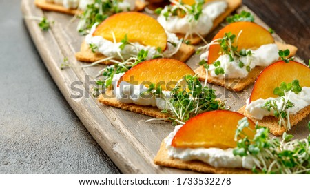 Cottage cheese and nectarine wedges on melba toast appetizers drizzled with runny honey and served with cress salad microgreen. Healthy party finger food