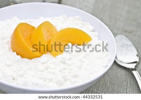Cottage cheese and peaches in a white bowl on a rustic background.